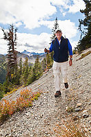 A man walking along a mountainside on a narrow trail.  Pacific Crest Trail, North Cascades of Washington, USA.