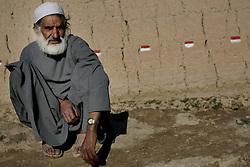 A bearded man sits by a wall in Qala-eQazi, Afghanistan.
