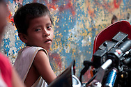 A young boy sits in front of a colorful wall in the Belen Market, in Iquitos, Peru.  The open-air market that winds through the narrow streets of Belen sells everything from medicinal remedies to alligator meat.