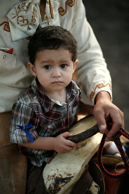 Julia Robinson photo.A young charro takes a ride around the lienzo with his father during a coleadero in Comfort, Texas