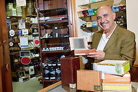 Portrait of a happy owner showing cigar boxes in store