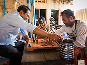24 FEBRUARY 2015 - PHNOM PENH, CAMBODIA:  Men play chess in a bar on the ground floor of the White Building in Phnom Penh. The White Building, the first modern apartment building in Phnom Penh, originally had 468 apartments, and was opened the early 1960s. The project was overseen by Vann Molyvann, the first Cambodian architect educated in France. The building was abandoned during the Khmer Rouge occupation. After the Khmer Rouge were expelled from Phnom Penh in 1979, artists and dancers moved into the White Building. Now about 2,500 people, mostly urban and working poor, live in the building. Ownership of the building is in dispute. No single entity owns the building, some units are owned by their occupants, others units are owned by companies who lease out apartments. Many of the original apartments have been subdivided since the building opened and serve as homes to two or three families. The building has not been renovated since the early 1970s and is in disrepair. Phnom Penh officials have tried to evict the tenants and demolish the building but residents refuse to move out.  PHOTO BY JACK KURTZ