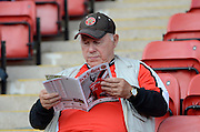 Walsall fan reading the match day programme during the Sky Bet League 1 match between Walsall and Doncaster Rovers at the Banks's Stadium, Walsall, England on 12 September 2015. Photo by Alan Franklin.