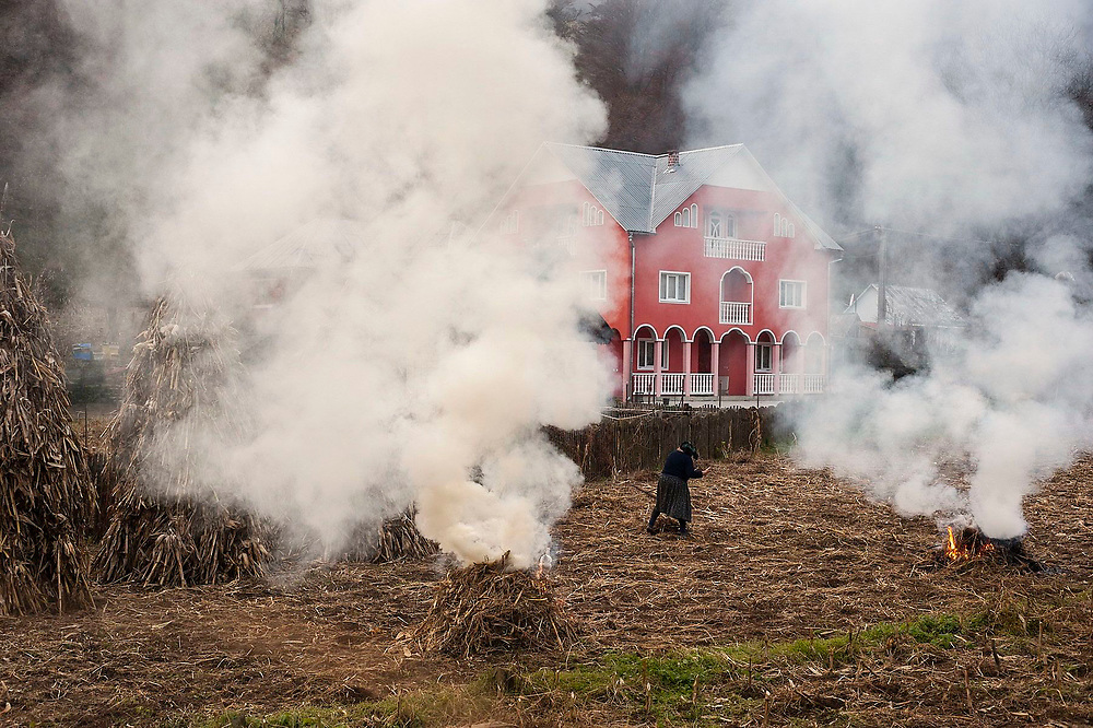 A local woman gathers straw off a field in front of a newly built house in Ilva Mare village. The straw is set alight and burnt in small fires.
