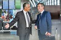 Mature businessman gesturing while talking to business partner in airport