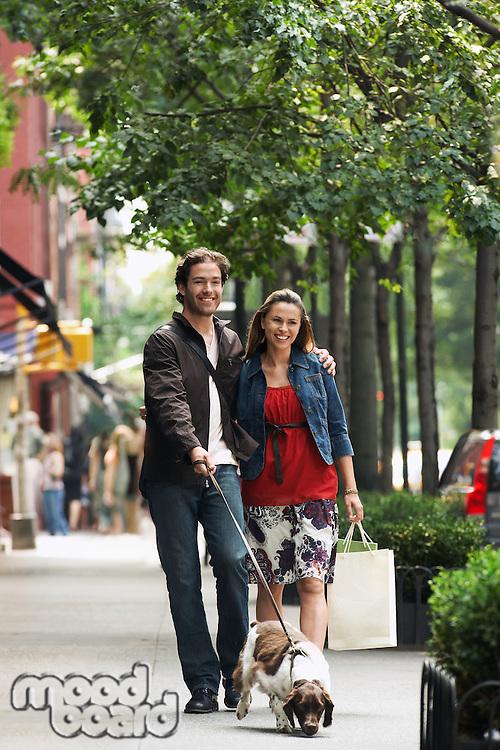Couple walking dog on sidewalk