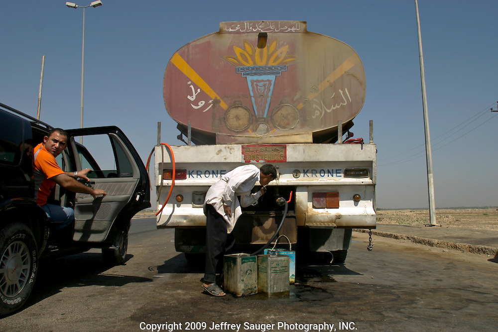 Haider Al-Jubury, left, watches the road as roadside gasoline seller siphons fuel from a tanker on the road to Baghdad, Iraq.