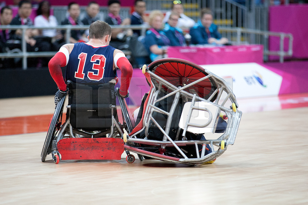 © London News Pictures. 05/09/2012. A wheelchair athlete gets tipped over in the wheelchair rugby competition. The opening game of the wheelchair rugby competition started today between ParalympicsGB and world champions USA at the Paralympic Games in Stratford, London, UK. Team USA won the match 56 - 44. Photo credit should read Manu Palomeque/LNP