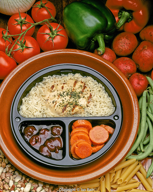 Diabetic Plate of Rice  & Chicken with Carrots and Fruit, surrounded by fresh vegetables beans and pasta.