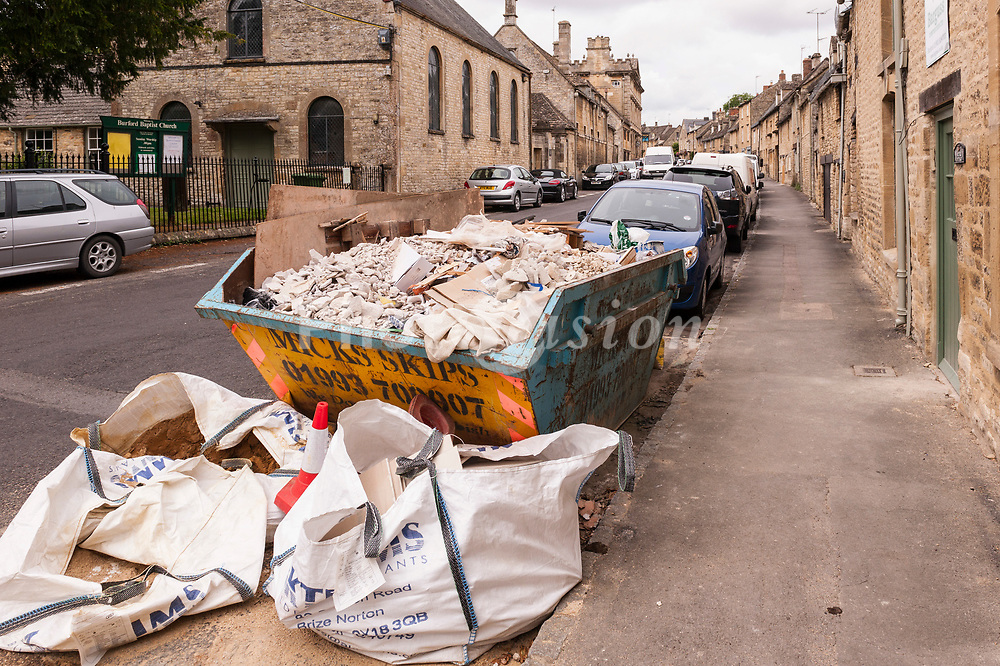 A builders skip spoils the view of the pretty Cotswold town of  Burford , Oxfordshire , England , Britain , Uk