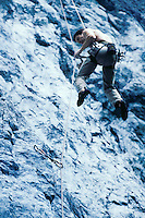 A rock climber being lowered off of a climb as he cleans the route of gear on the way down.