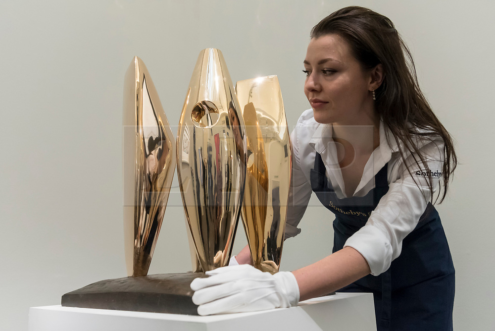 """© Licensed to London News Pictures. 16/11/2018. LONDON, UK. A technician presents """"Four Figures Waiting"""", 1968, by Dame Barbara Hepworth (Est. GBP350,000-450,000). Preview of Sotheby's autumn sale of Modern & Post War British art.  Works from the British art scene of the past century will be offered for sale on 20 and 21 November 2018 at Sotheby's in London.  Photo credit: Stephen Chung/LNP"""
