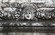 Mask and garland frieze, Aphrodisias, Aydin, Turkey. The Sculpture School at Aphrodisias was an important producer of carved marble sarcophagi and friezes from the 1st century BC until the 6th century AD. The city has many examples of mask and garland friezes, consisting of heads of gods or theatrical masks between hanging garlands of leaves, fruit and flowers. This example is possibly a Medusa. The best examples of these were from the Portico of Tiberius, the Southern portico of the Agora. Aphrodisias was a small ancient Greek city in Caria near the modern-day town of Geyre. It was named after Aphrodite, the Greek goddess of love, who had here her unique cult image, the Aphrodite of Aphrodisias. The city suffered major earthquakes in the 4th and 7th centuries which destroyed most of the ancient structures. Picture by Manuel Cohen
