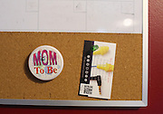 """A """"Mom to Be"""" pin is pinned up to a bulletin board Saturday in Vina inside the home of Brandon and Melissa Kennedy. The remoteness of their home and lack of access provided in Alabama requires the Kennedys to travel over 50 minutes to their OB-GYN appointments and to deliver their baby."""