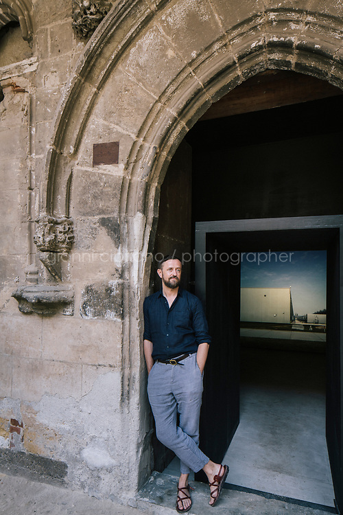 PALERMO, ITALY - 15 JUNE 2018: Artist John Gerrard poses for a portrait at the entrance to his video simulation &quot;Farm (Council Bluffs, Iowa)&quot; (2015) at Palazzo Ajutamicristo during Manifesta 12, the European nomadic art biennal, in Palermo, Italy, on June 15th 2018.<br /> <br /> Manifesta is the European Nomadic Biennial, held in a different host city every two years. It is a major international art event, attracting visitors from all over the world. Manifesta was founded in Amsterdam in the early 1990s as a European biennial of contemporary art striving to enhance artistic and cultural exchanges after the end of Cold War. In the next decade, Manifesta will focus on evolving from an art exhibition into an interdisciplinary platform for social change, introducing holistic urban research and legacy-oriented programming as the core of its model.<br /> Manifesta is still run by its original founder, Dutch historian Hedwig Fijen, and managed by a permanent team of international specialists.<br /> <br /> The City of Palermo was important for Manifesta&rsquo;s selection board for its representation of two important themes that identify contemporary Europe: migration and climate change and how these issues impact our cities.
