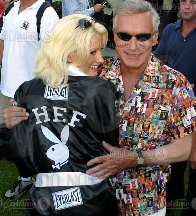Jul 09, 2002; Los Angeles, CA, USA; HUGH HEFNER helps playmate HOLLY MADISON model his fight robe @ SUGAR RAY LEONARD BOXING first year anniversary was celebrated with a live fight night on ESPN2 from the Playboy Mansion in Holmby Hills.  Over 350 invited guests attended the cocktail reception and showdown in the back yard of Playboy HUGH HEFNER's 5 1/2 acre estate. <br />