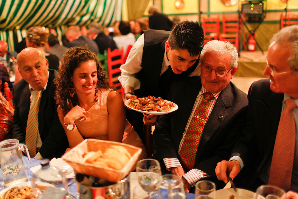 "Abril, 19, 2010. Lifestyle/Spain. Seville April Fair. Night of ""pescaito"" starts the week of April Fair of Seville. The evening starts with a dinner by all members of the ""caseta"" (fraternity) based in fried fish and seafood. At twelve o'clock at night lights up the ""portada"" (cover at main entrance) and  the fairgrounds with ""el alumbrao"" giving the official kickoff of the fair...La noche del ""pescaíto"" da inicio a la semana de la feria de abril de Sevilla. La noche empieza con una cena entre todos los miembros de la caseta a base de pescado frito y marisco. A las doce de la noche se ilumina la portada con ""el alumbrao"" y todo el recinto ferial dando así inicio oficial a la feria."