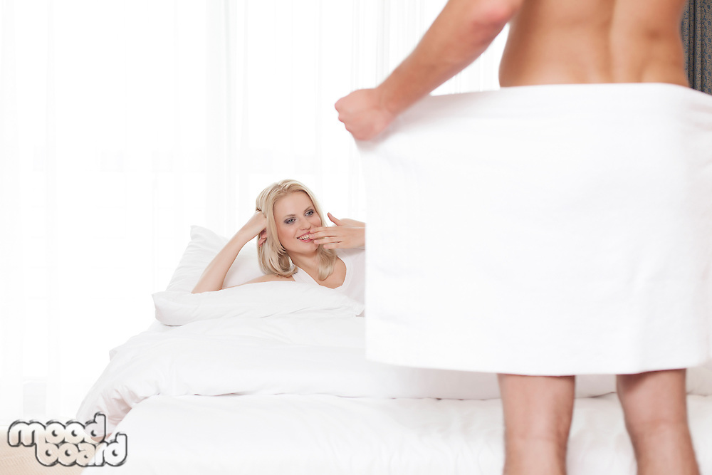 Surprised woman looking at nude man holding towel in bedroom