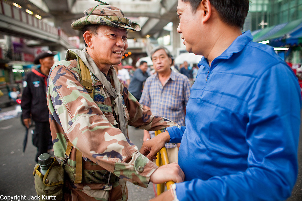 "May 12 - BANGKOK, THAILAND: Maj. Gen. KHATTIYA ""Seh Daeng"" SAWASDIPOL (LEFT) talks to a Red Shirt ""civilian"" at a Red Shirt barricade in the Red Shirt camp in Bangkok Wednesday. Seh Daeng, as he is known, has emerged as the Red Shirts unofficial military commander. He has organized the barricades that ring the Red Shirt camp and has threatened to organize a guerilla campaign against the government if the Red Shirt protest is crushed by force. Seh Daeng is a hero to many Thais because he is credited with crushing Thailand's communist insurgency in the 1970's and 80's. He was the commander of Thailand's Internal Security Operations Command but after his political activities became apparent he was made the head aerobics instructor for the Thai army. He is now seen as one of the major personalities destabilizing the country and the government alleges that he is behind many of the grenade attacks and drive by shootings directed at government buildings and officials and he is wanted for a long list of felony offenses including weapons charges and terrorism related charges. Although some Red Shirts have officially repudiated him, he is still frequently seen around the Reds' barricades. The army has started proceedings to fire him, but he remains a general on active duty.   Photo by Jack Kurtz"