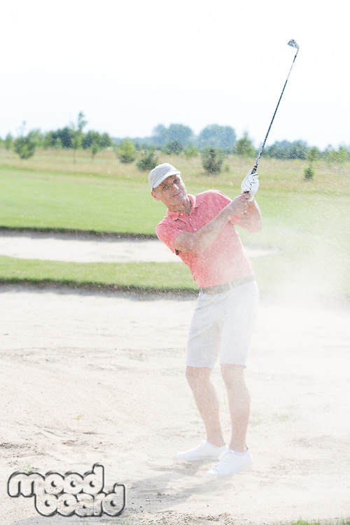 Middle-aged man playing at golf course