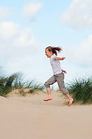 Young girl running on beach side view