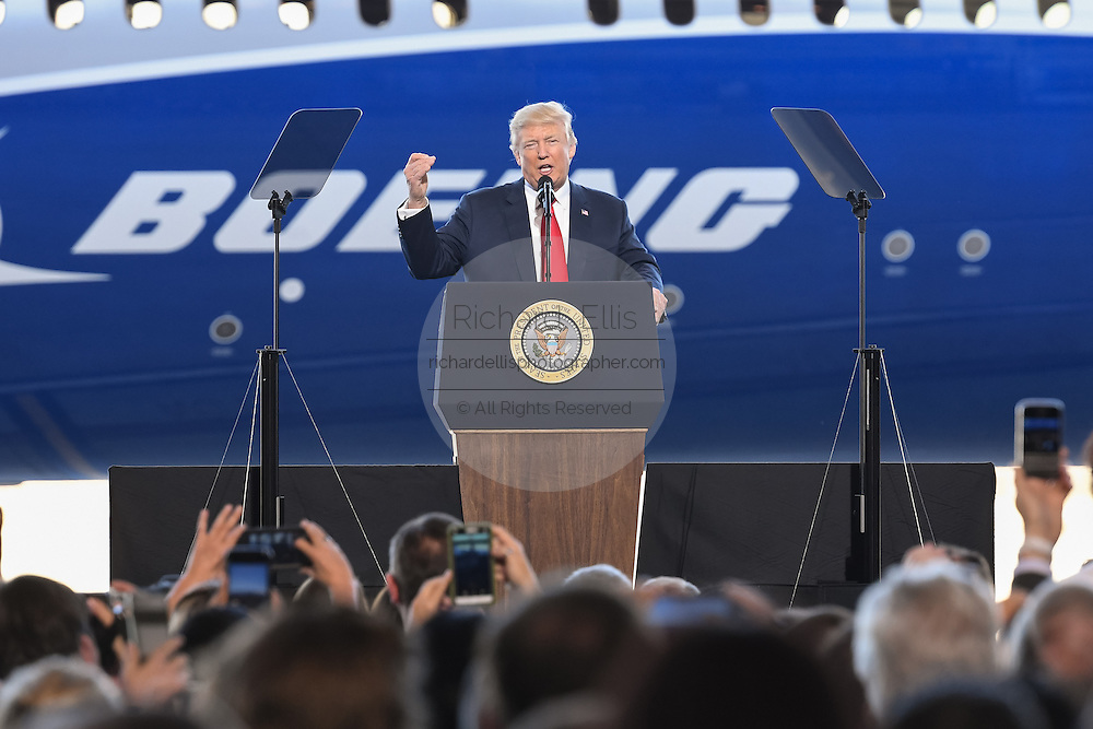U.S. President Donald Trump points to the new Boeing 787-10 Dreamliner aircraft during his address to employees at the Boeing factory February 17, 2016 in North Charleston, SC. The visit comes two days after workers at the South Carolina plant voted to reject union representation in a state where Trump won handily.