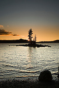 Island silhouette on Waldo Lake 1650m (5,414ft), with sunset over Klovdahl Bay.  Viewed from Shadow Bay on the east shore.  Waldo Lake is the headwaters of the North Fork of the Middle Fork of the Willamette River, and the only lake in the Oregon Scenic Waterways System.