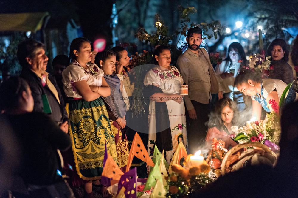 Family members light candles and gather around the gravesite of a family member during the Day of the Dead festival October 31, 2017 in Tzintzuntzan, Michoacan, Mexico.