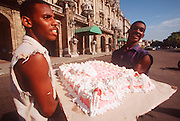 CUBA, HAVANA (CENTRO HABANA) young men carrying a huge cake across the Paseo de Marti in Havana