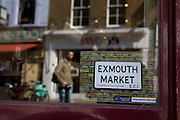 Reflections and an Exmouth market postcard on display in the window of Moro restaurant in Exmouth market, London.