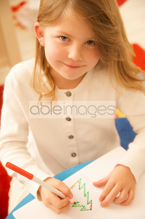 Smiling girl writing a letter to Father Christmas