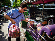 20 JUNE 2018 - BANGKOK, THAILAND: A tuk-tuk (three wheeled taxi) puts a passenger's plastic bags of rambutan (a type of fruit) into his tuk-tuk at Makkasan Market, a small local market in central Bangkok. Officials in Thailand are wrestling with Thais use of plastic bags. The issue became a public one in early June when a whale in Thai waters died after ingesting 18 pounds of plastic. In a recent report, Ocean Conservancy claimed that Thailand, China, Indonesia, the Philippines, and Vietnam were responsible for as much as 60 percent of the plastic waste in the world's oceans.    PHOTO BY JACK KURTZ