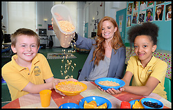 Eastenders actress Patsy Palmer serves breakfast to L to r Ryan Tappin 10, and Rehana Jardenier 10, on a visit to Laycock Primary School in Islington, London, to take part in London's Biggest Breakfast. Thursday, 22nd May 2014. Picture by Andrew Parsons / i-Images.<br /> <br /> Patsy Palmer goes back to school to host a hearty breakfast in support of 'London's Biggest Breakfast Campaign' <br /> <br /> The EastEnders Actress is having breakfast with children from Laycock Primary School Breakfast Club in Islington to raise money for London youth charity, the Mayor's Fund for London.