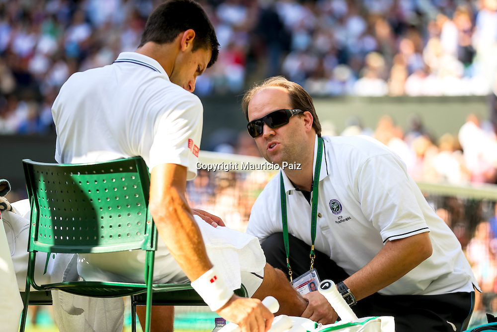 LONDON, ENGLAND - JULY 6: Novak Djokovic of Serbia gets medical treatment  during the Gentlemens' Singles final match against Roger Federer of Switzerland on day thirteen of the Wimbledon Lawn Tennis Championships at the All England Lawn Tennis and Croquet Club at Wimbledon on July 6, 2014 in London, England.