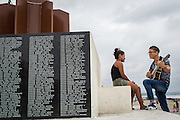 2016/10/08 – Pedernales, Ecuador: A boy plays a serenade to a girl on the memorial to the victims of the 16th April earthquake, Pedernales, Ecuador, 8th October 2016. Pedernales was the epicentre of the earthquake, which destroyed much of the city and killed 188 people. (Eduardo Leal)