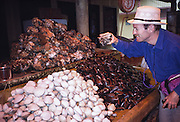 "Dave shops for clams and mussels (bivalve molluscs) at a seafood market in Puerto Montt, Los Lagos Region, Zona Austral, Chile, South America. What international tourist literature calls the ""Chilean Lake District"" usually refers to the Andean foothills between Temuco and Puerto Montt including three Regions (XIV Los Ríos, IX La Araucanía, and X Los Lagos) in what Chile calls the Zona Sur (Southern Zone). In Chile, Patagonia includes the territory of Valdivia through Tierra del Fuego archipelago. Spanning both Argentina and Chile, the foot of South America is known as Patagonia, a name derived from coastal giants (""Patagão"" or ""Patagoni"" who were actually Tehuelche native people who averaged 25 cm taller than the Spaniards) who were reported by Magellan's 1520s voyage circumnavigating the world. For licensing options, please inquire."