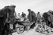 A man places his firewood which is being rationed out into a wheelbarrow at the IDP Charahi Qambar refugee camp.