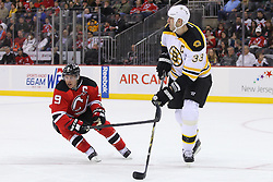 Jan 4, 2012; Newark, NJ, USA; Boston Bruins defenseman Zdeno Chara (33) makes a pass while being defended by New Jersey Devils left wing Zach Parise (9) during the second period at the Prudential Center.