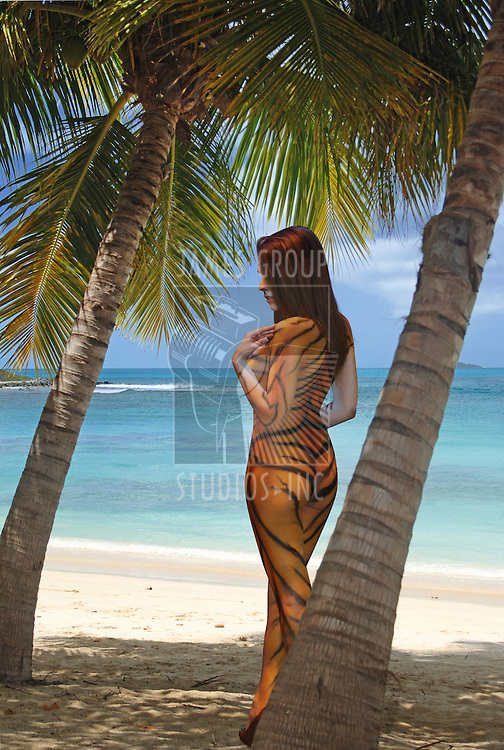 A nude painted woman between two Palm trees on the beach.