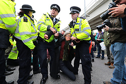 © Licensed to London News Pictures. 10/10/2019. London, UK. Police arrest Extinction Rebellion protesters as they block road access to London City Airport. Protesters plan to occupy the terminal building in a 'Hong Kong-style' shutdown as part of ongoing protests calling on government departments to tackle the Climate Emergency. Photo credit: Rob Pinney/LNP
