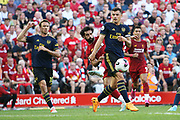 Liverpool forward Mohamed Salah (11) bends a shot round Arsenal midfielder Granit Xhaka (34)  during the Premier League match between Liverpool and Arsenal at Anfield, Liverpool, England on 24 August 2019.