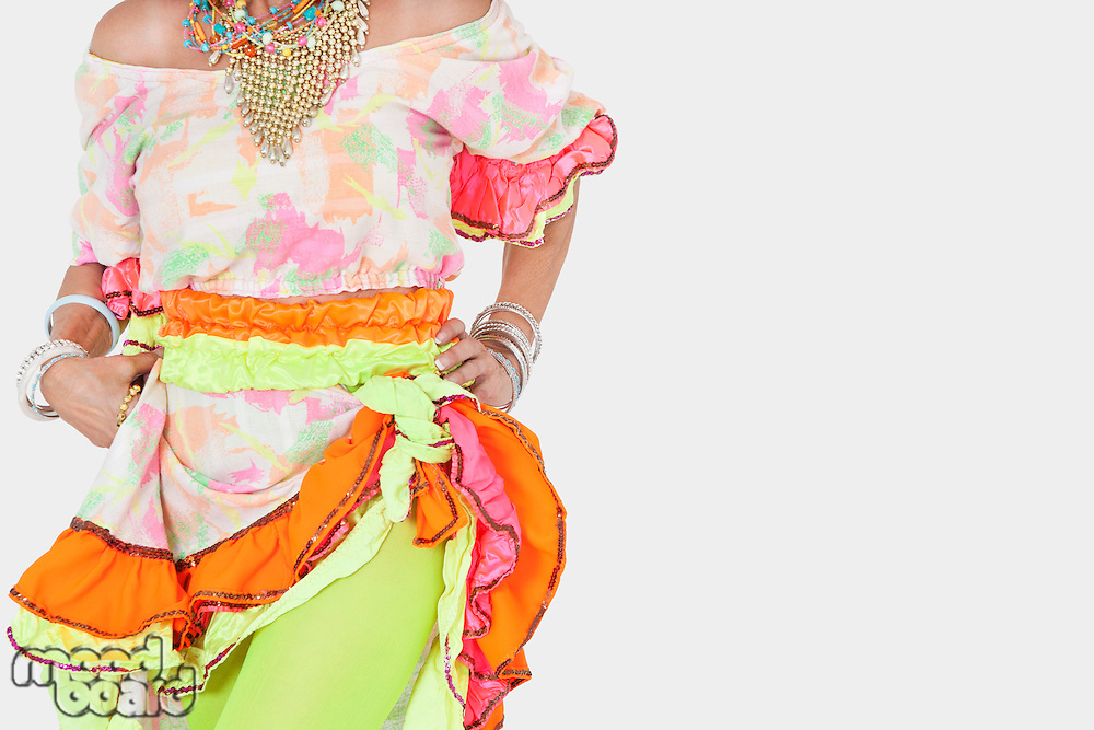 Midsection of senior woman in Brazilian costume over gray background