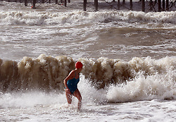 A swimmer braves the rough seas on the beach at Brighton as the South Coast braces itself for the storm, Sunday, 27th October 2013. Picture by Stephen Lock / i-Images