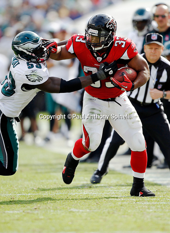 Atlanta Falcons running back Michael Turner (81) gets tackled by Philadelphia Eagles linebacker Moise Fokou (53) during the NFL week 6 football game against the Philadelphia Eagles on Sunday, October 17, 2010 in Philadelphia, Pennsylvania. The Eagles won the game 31-17. (©Paul Anthony Spinelli)