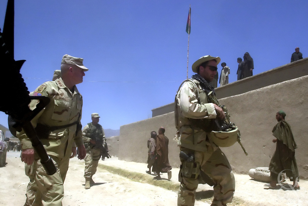 U.S. Army General Dan McNeill (L), Coalition Joint Task Force 180 commander, is escorted by Special Forces soldiers during a July 7, 2002 personal visit to Deh Rawud in Southern Afghanistan. McNeill used the visit to speak with the regional governor Jan Mohammed Khan and local elders about the possibility of stationing more U.S. troops in the region, following an incident last week in which U.S. aircraft mistakenly targeted Afghan civilians celebrating in Deh Rawud