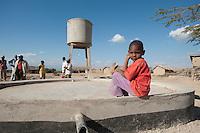 07 OCT 2009, MOSHI/TANZANIA:<br /> Kind eines Dorfes, das durch ein von der KfW finanziertes Projekt eine Trinkwasserversorgung durch einen Hochtank (im Hintergrund) erhalten hat, ONE Informationsreise nach Tansania, Moshi / Kilimandschro<br /> IMAGE: 20091007-01-295<br /> KEYWORDS: Reise, Trip, Entwicklungshilfe, Afrika, Africa, Kind, children, child, Wasserversorgung, Trinkwasser, Wasser