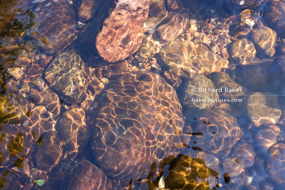 Ripples reflected onto shiny surfaces of rocks and pebbles in the River Enz in Germany's Black Forest.