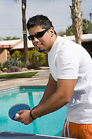 Young Man Playing Ping-Pong by Swimming Pool