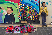 Young indigenous girl selling woven goods in front of mural, Otavalo, Ecuador