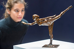 "© Licensed to London News Pictures. 20/02/2019. LONDON, UK. A staff member views ""Danseuse, Arabesque ouverte sur la jambe droite, bras, gauche dans la ligne"", 1919, by Edgar Degas (Est. £0.6-0.8m).  Preview of Sotheby's Impressionist & Modern and Surrealist Art sales.  The auction will take place at Sotheby's New Bond Street on 26 February 2019.  Photo credit: Stephen Chung/LNP"